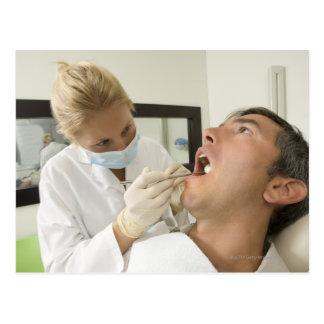 Hombre de examen del dentista de sexo femenino tarjetas postales