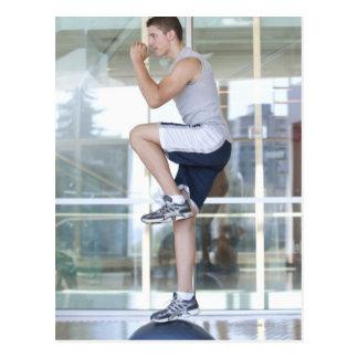 hombre joven que hace ejercicios elevadores en un  tarjetas postales