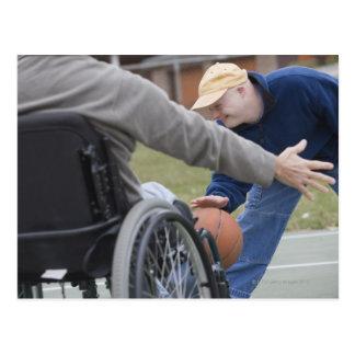 Hombre lisiado que juega a baloncesto con su hijo postal