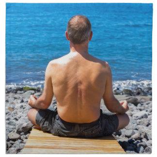 Hombre meditating en la playa y el mar servilleta de tela