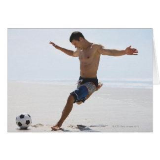 Hombre que golpea el balón de fútbol con el pie en tarjeta