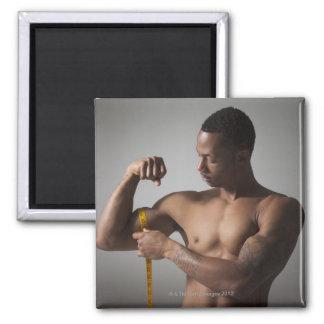 Hombre que mide su tríceps iman de frigorífico