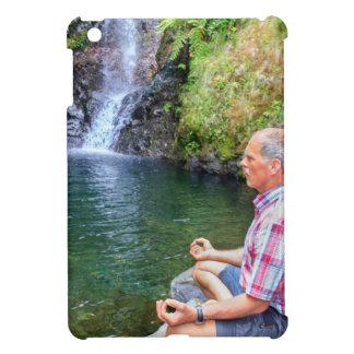 Hombre que se sienta en la roca meditating cerca