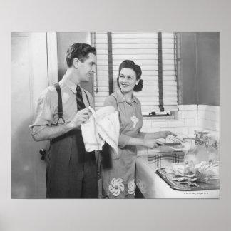 Hombre y mujer que hacen platos posters