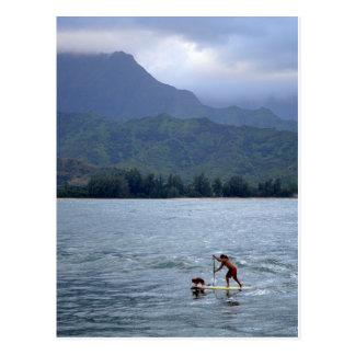 Hombre y perro en Paddleboard en postal de la