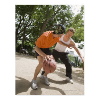Hombres que juegan a baloncesto al aire libre postal