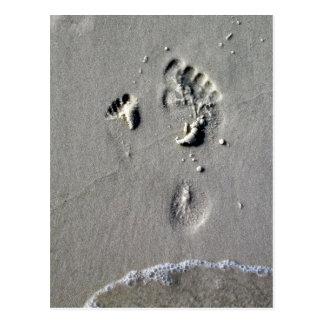 Huellas del padre y del niño en la arena postal