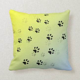 Huellas frescas del gato con el fondo amarillo cojin