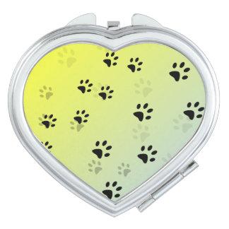 Huellas frescas del gato con el fondo amarillo espejos compactos
