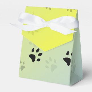 Huellas frescas del gato con el fondo amarillo paquetes de regalo para fiestas