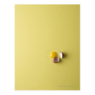 huevo agrietado en fondo amarillo postal