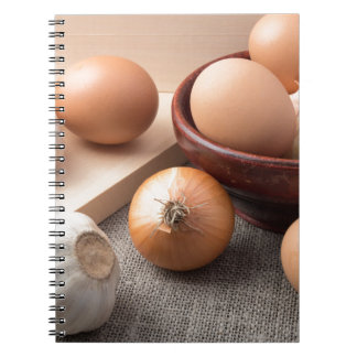 Huevos, cebollas y ajo crudos en un fondo cuaderno