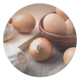 Huevos, cebollas y ajo crudos en un fondo plato de comida