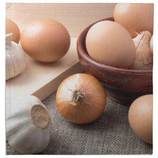 Huevos, cebollas y ajo crudos en un fondo servilleta de tela