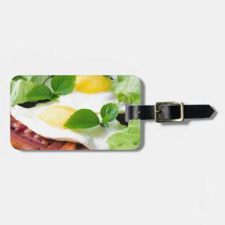 Huevos fritos con las hierbas, la lechuga y el etiqueta para maletas