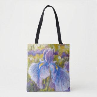 Iris azul y lirios púrpuras en la bolsa de asas