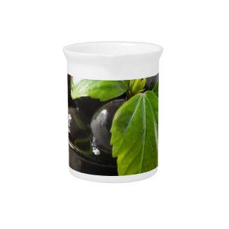 Jarra Aceitunas negras en una tabla y las tazas del