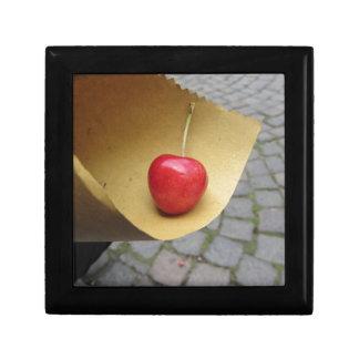 Joyero Una cereza roja en el papel de la comida de la