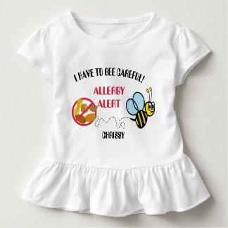 La alarma de la alergia de la nuez manosea la camiseta de bebé
