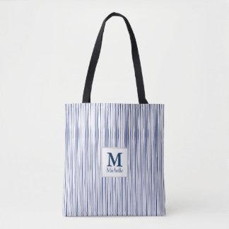 La bolsa de asas azul del monograma del modelo