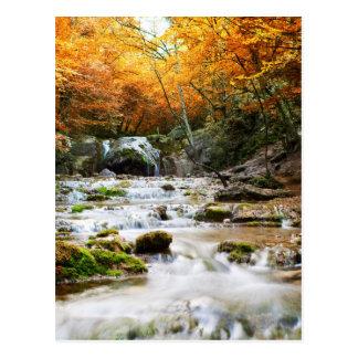La cascada hermosa en el bosque, otoño postal