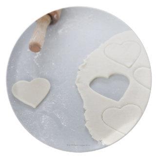 La forma del corazón cortó de una hoja de la pasta platos para fiestas