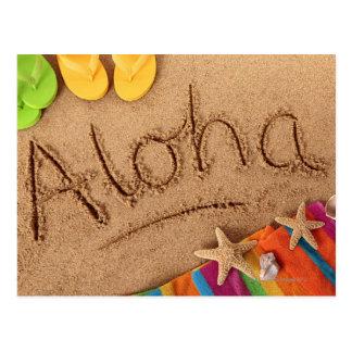 La hawaiana de la palabra escrita en una playa are postal