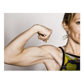 La hembra rubia joven dobla el músculo del bíceps postal
