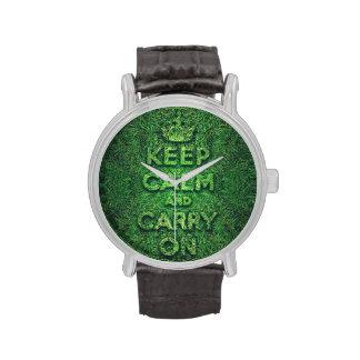 La hierba verde guarda calma y continúa relojes de mano