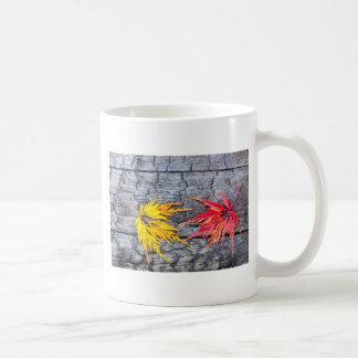 La hoja de arce amarilla y roja en negro quemó la taza de café