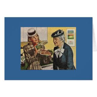 La mujer del vintage muestra la cazuela a la tarjeta