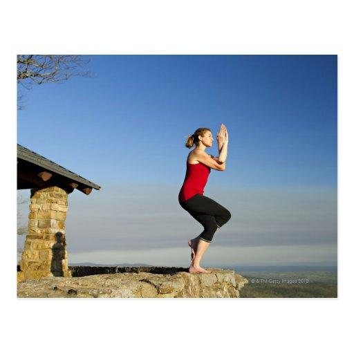 la mujer joven practica yoga en un pen¢asco en tarjetas postales