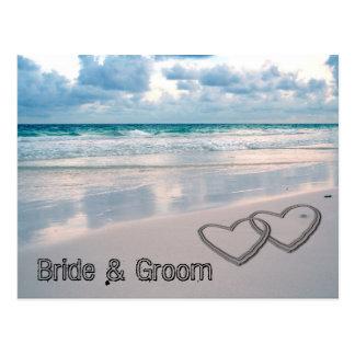 La novia y el novio nombra escrito en la arena postal