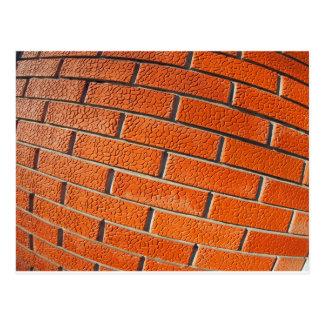 La pared de ladrillos rojos decorativos se cierra postal