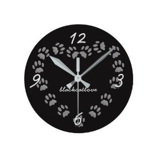 La pata del amor del gato negro imprime el reloj