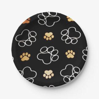 La pata del perrito del perro imprime negro y el plato de papel