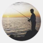 La pesca del hombre joven en la puesta del sol de pegatinas redondas