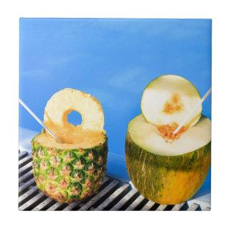La piña y el melón dan fruto con la paja en la azulejo de cerámica