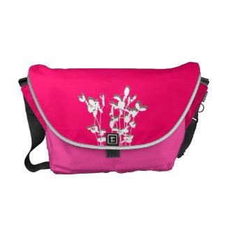 La planta creciente rosada de dos tonos sale de la bolsa messenger