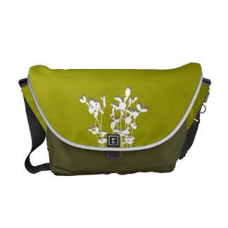 La planta creciente verde de dos tonos sale de la  bolsas de mensajeria