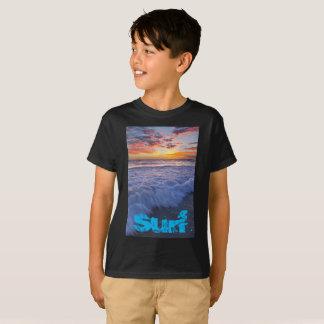 La playa que practica surf agita en la puesta del camiseta