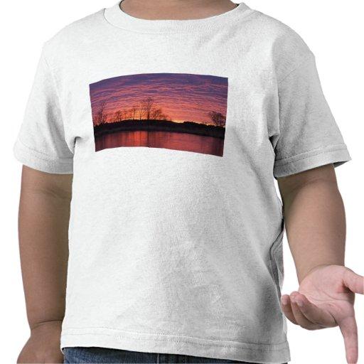 La puesta del sol brillante refleja en el río del  camiseta