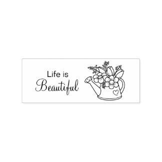 La regadera del jardín con vida de las flores es sello de caucho