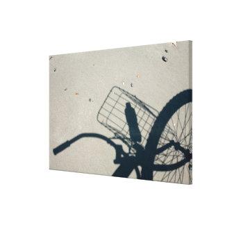La sombra de una bicicleta con una botella de agua lona envuelta para galerias