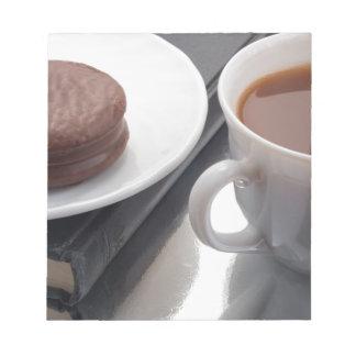 La taza blanca con cacao y chocolate cubrió la bloc de notas