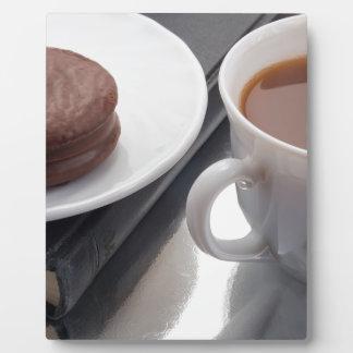 La taza blanca con cacao y chocolate cubrió la placa expositora