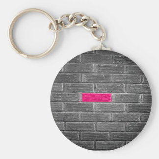 Ladrillo rosado en una pared negra y blanca llaveros