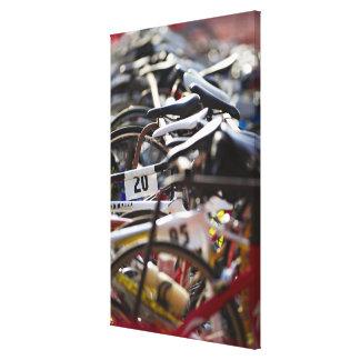 Las bicicletas en el estante en un triathlon compi impresiones en lona estiradas