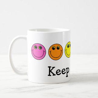 Las caras sonrientes coloridas guardan el sonreír taza de café