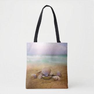 Las cáscaras en la playa con el océano azul riegan bolsa de tela